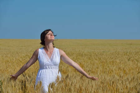 Young woman standing jumping and running  on a wheat field with blue sky the background at summer day representing healthy life and agriculture concept Stock Photo - 14862636