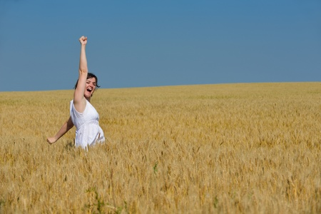 Young woman standing jumping and running  on a wheat field with blue sky the background at summer day representing healthy life and agriculture concept photo