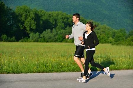 ジョグ: 若いカップルは、朝の公園でジョギングします。健康とフィットネス