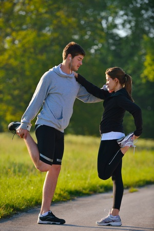 spring training: young health couple doing stretching exercise relaxing and warm up after jogging and running in park