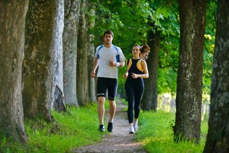 若いカップルは、朝の公園でジョギングします。健康とフィットネス