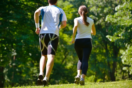 training shoes: Young couple jogging in park at morning. Health and fitness.