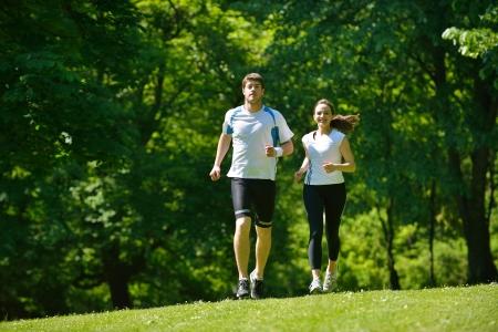 Jong paar joggen in het park bij 's morgens. Gezondheid en fitness.