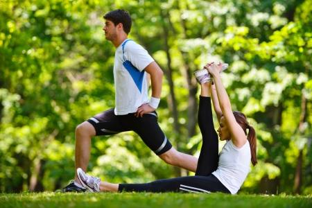 piernas hombre: pareja joven haciendo salud ejercicios de estiramiento y relajaci�n calentarse despu�s de trotar y correr en el parque Foto de archivo