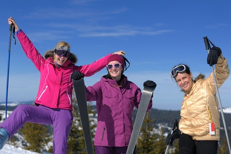 happy friends group of woman girls have fun at winter season at beautiful sunny  snow day with blue sky in background Stock Photo