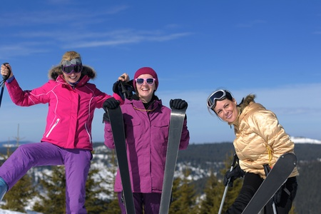 happy friends group of woman girls have fun at winter season at beautiful sunny  snow day with blue sky in background photo