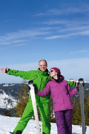 Portrait of happy couple at beautiful mountain on winter sunny day with blue sky and snow in background photo