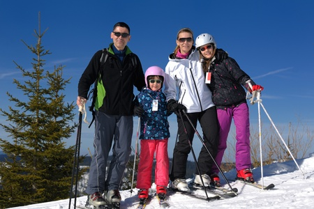 portrait of happy young family at beautiful winter sunny day with blue sky and snow in background photo