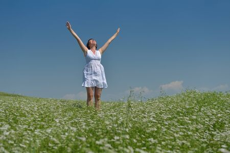 Young happy woman in green field with blue sky in background photo