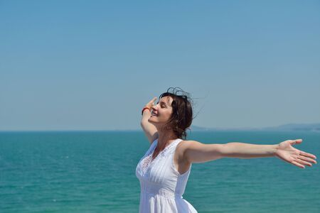 free backgrounds: Happy  young woman with spreading arms, blue sky with clouds in background  - copyspace