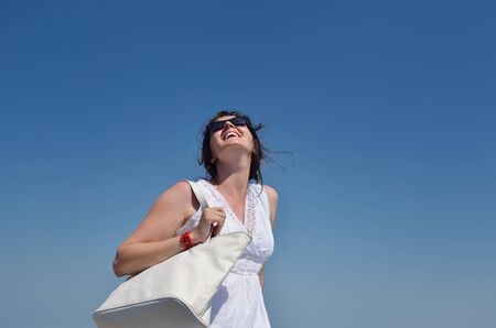 happy young tourist woman have fun while traveling araund city with blue sky and sea in background photo