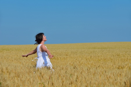 Young woman standing jumping and running  on a wheat field with blue sky in  background at summer day representing healthy life and agriculture concept photo