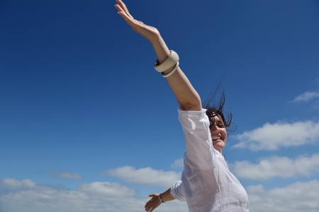 woman freedom: Happy  young woman with spreading arms, blue sky with clouds in background  - copyspace