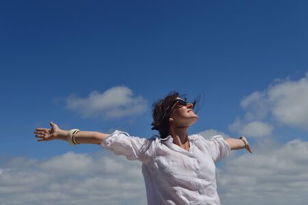 Happy  young woman with spreading arms, blue sky with clouds in background  - copyspace photo