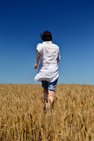 Young woman standing jumping and running  on a wheat field with blue sky in  background at summer day representing healthy life and agriculture concept Stock Photo - 15162077