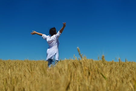 Young woman standing jumping and running  on a wheat field with blue sky in  background at summer day representing healthy life and agriculture concept Stock Photo - 15161821