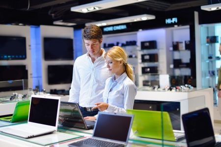 consumer electronics: people in consumer electronics  retail store looking at latest laptop, television and photo camera to buy