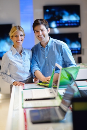 computer model: people in consumer electronics  retail store looking at latest laptop, television and photo camera to buy