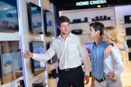 people in consumer electronics  retail store looking at latest laptop, television and photo camera to buy Stock Photo - 15275808