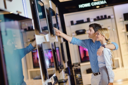 people in consumer electronics  retail store looking at latest laptop, television and photo camera to buy Stock Photo - 15275796