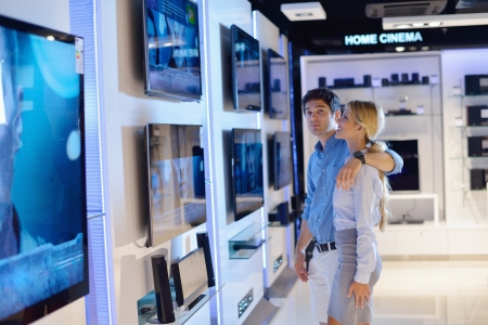 people in consumer electronics  retail store looking at latest laptop, television and photo camera to buy Stock Photo - 15241674