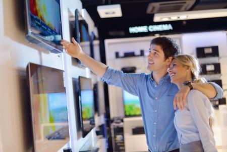 gl�cklicher kunde: Menschen in der Unterhaltungselektronik Einzelhandel Blick auf neuesten Laptop, Fernsehen und Foto-Kamera zu kaufen Lizenzfreie Bilder