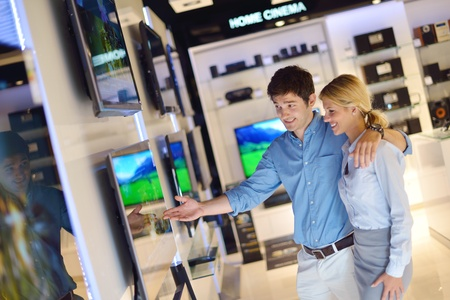flat screen television: people in consumer electronics  retail store looking at latest laptop, television and photo camera to buy