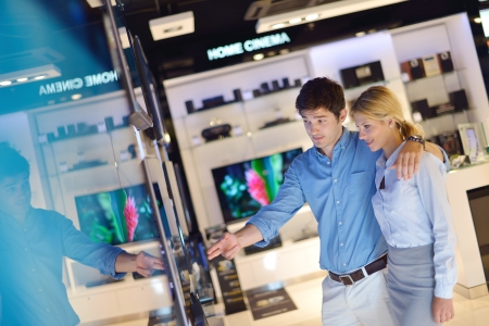people in consumer electronics  retail store looking at latest laptop, television and photo camera to buy Stock Photo - 15241437