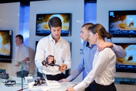 people in consumer electronics  retail store looking at latest laptop, television and photo camera to buy Stock Photo - 15242070