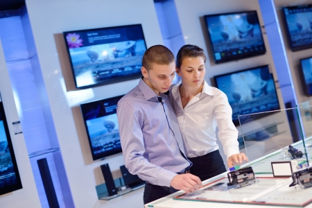 people in consumer electronics  retail store looking at latest laptop, television and photo camera to buy Stock Photo - 15242194