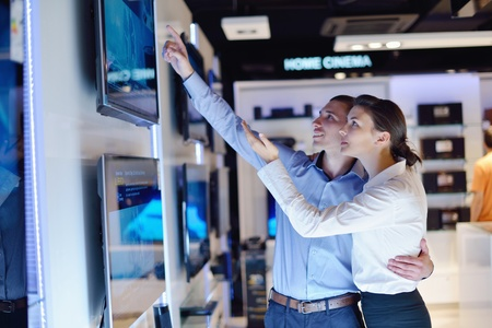 people in consumer electronics  retail store looking at latest laptop, television and photo camera to buy Stock Photo - 15242069