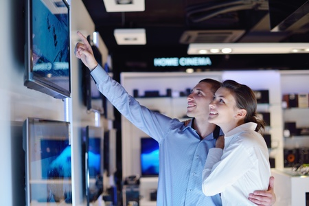 people in consumer electronics  retail store looking at latest laptop, television and photo camera to buy Stock Photo - 15242142