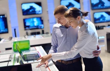 consommateurs: personnes dans un magasin d'?lectronique de d?tail en regardant la cam?ra dernier ordinateur portable, la t?l?vision et la photo pour acheter