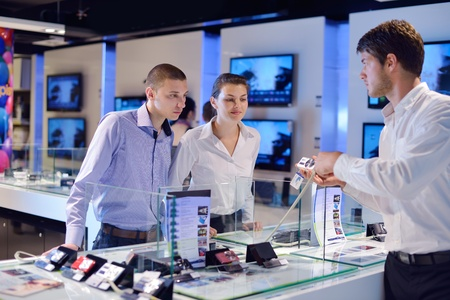 people in consumer electronics  retail store looking at latest laptop, television and photo camera to buy photo