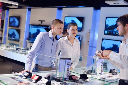people in consumer electronics  retail store looking at latest laptop, television and photo camera to buy Stock Photo - 15241255