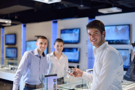 people in consumer electronics  retail store looking at latest laptop, television and photo camera to buy Stock Photo - 15241178