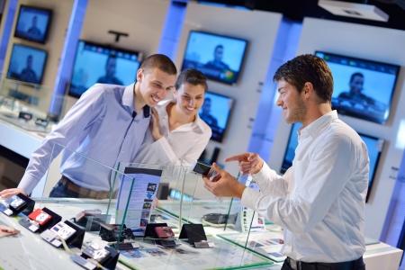 Menschen in der Unterhaltungselektronik Einzelhandel Blick auf neuesten Laptop, Fernsehen und Foto-Kamera zu kaufen
