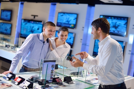 people in consumer electronics  retail store looking at latest laptop, television and photo camera to buy Stock Photo - 15242015