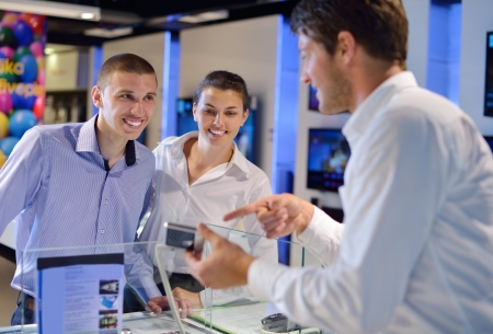 customer service woman: people in consumer electronics  retail store looking at latest laptop, television and photo camera to buy