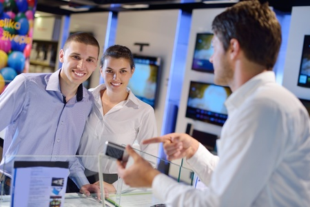 people in consumer electronics  retail store looking at latest laptop, television and photo camera to buy Stock Photo - 15241808