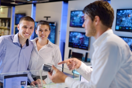 people in consumer electronics  retail store looking at latest laptop, television and photo camera to buy Stock Photo - 15241286