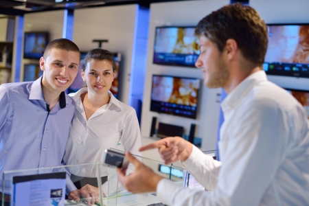 people in consumer electronics  retail store looking at latest laptop, television and photo camera to buy Stock Photo - 15242016