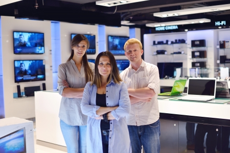 people in consumer electronics  retail store looking at latest laptop, television and photo camera to buy Stock Photo - 15241492