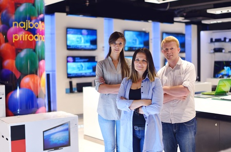 people in consumer electronics  retail store looking at latest laptop, television and photo camera to buy Stock Photo - 15241740
