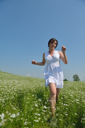 free running: Young happy woman in green field with blue sky in background Stock Photo