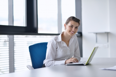 office windows: Young pretty business woman with notebook in the bright modern office indoors