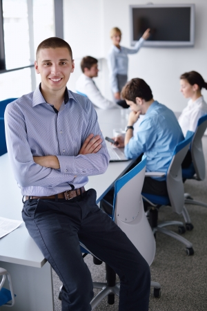 Portrait of a handsome young  business man  on a meeting in offce with colleagues in background photo