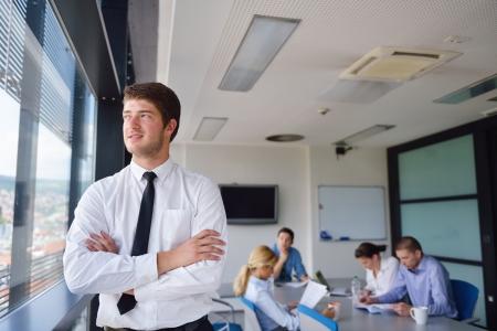 lideres: Retrato de un hombre de negocios joven guapo en una reunión en offce con los colegas en el fondo