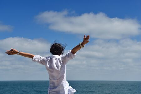 spreading arms: Happy  young woman with spreading arms, blue sky with clouds in background  - copyspace