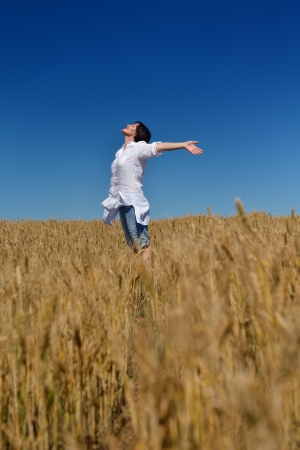 Young woman standing jumping and running  on a wheat field with blue sky in  background at summer day representing healthy life and agriculture concept Stock Photo - 15511956